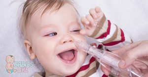Toddler having their nasal mucus removed with an aspirator