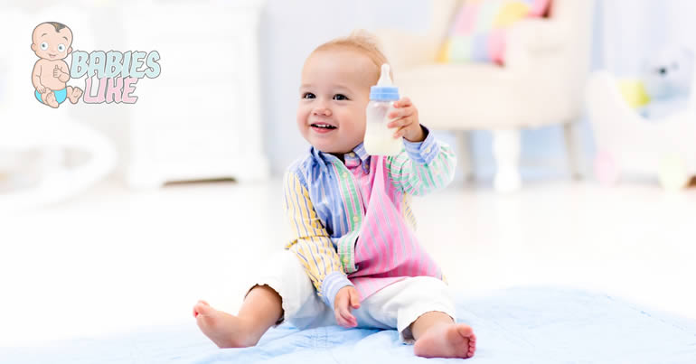 Smiling toddler holding a bottle full of formula