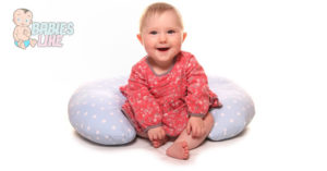 Baby using a boppy pillow for support.