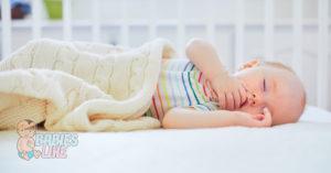 Baby asleep in a mini crib lying on a comfortable mattress